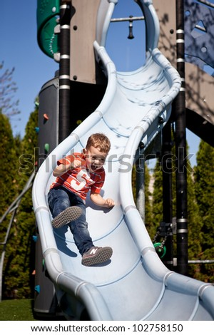 Little boy on the playground slide - stock photo