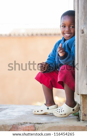 Little boy outside on the porch of his home.