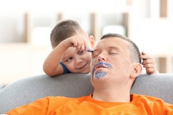 Little boy painting his father's face while he sleeping. April fool's day prank