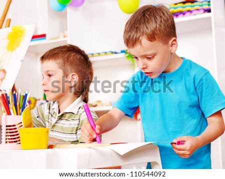 Little boy painting  in kindergarten.