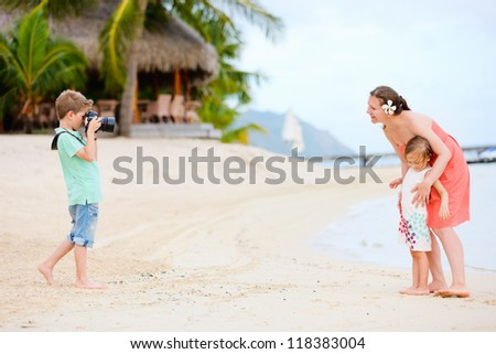 Little boy photographing his mother and sister at beach