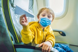 Little boy play with paper plane in the commercial jet airplane flying on vacation Tourists fear the 2019-ncov virus. Medical masked tourists
