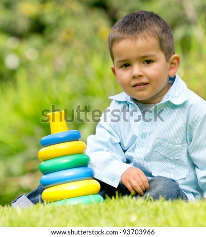 Little boy playing at the park with some toys