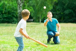 Little Boy Playing Baseball With His Father In Park