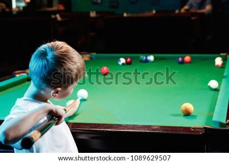 little boy playing billiards, recreation, entertainment, children's sports.