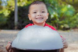 Little boy playing blowing and making soap bubbles holding bubble in his hand