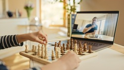 Little Boy Playing Chess with His Chess Master, Uses Laptop for Video Call. Child Learns how To Play Chess Through Internet. Remote Online Education, E-Education, Distance Learning. Over Shoulder