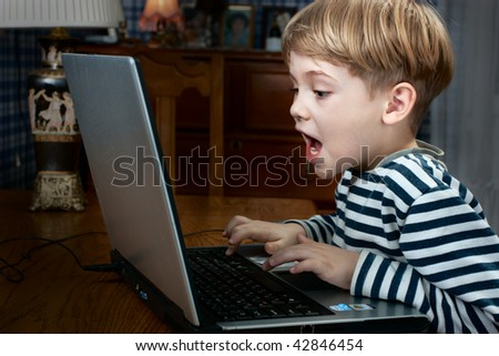 little boy playing computer game very emotional