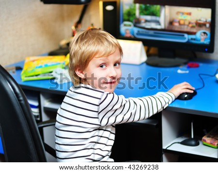 little boy playing computer games at home
