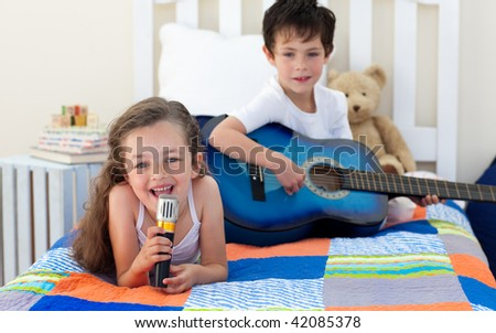 Little boy playing guitar and his sister singing in the bedroom