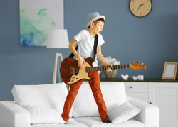 Little boy playing guitar ans singing on a sofa at home
