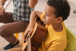Little boy playing guitar at music school