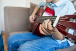 little boy playing guitar. close up of fingers and guitar frets