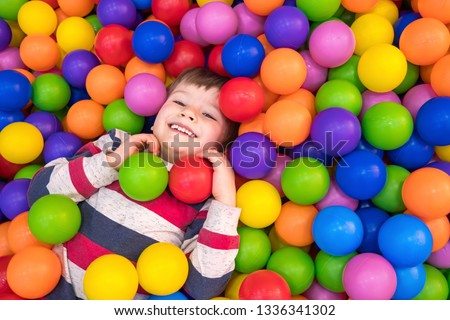 Little boy playing in dry pool with plastic balls in the nursery. Close-up leisure activities indoors. Positive emotions background. School holidays. Copy space #1336341302