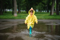 Little boy playing in rainy summer park. Child with umbrella, waterproof coat and boots jumping in puddle and mud in the rain. Kid walking in summer rain Outdoor fun by any weather. happy childhood