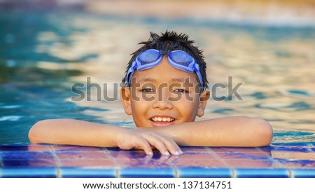 little boy playing in swimming pool under sunset light on the face