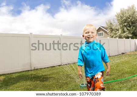Little Boy Playing in the sprinklers. Summertime fun - stock photo