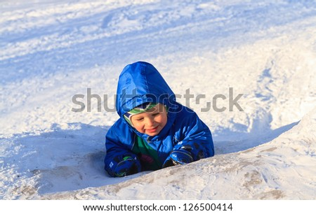 little boy playing in winter snow
