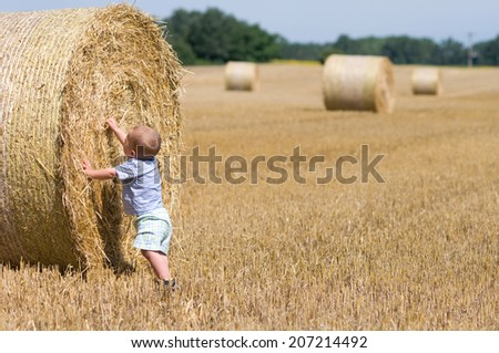 little boy playing on bales of straw on the field