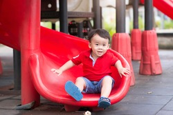 Little boy playing on children's slides. Outdoor portrait of a cute little asian boy at playground