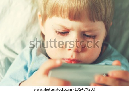 Little Boy Playing on Smartphone, Sitting in Room, toned image