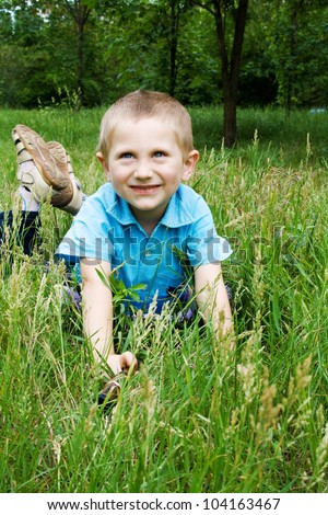 Little boy playing outdoors, lying on green grass - stock photo