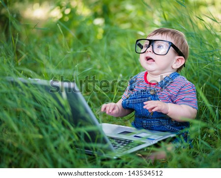 little boy playing outdoors with a laptop