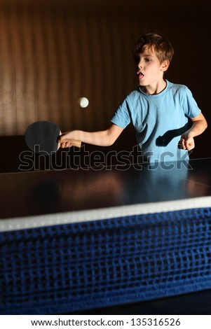 little boy playing ping pong; concentrated face; boy stuck out his tongue