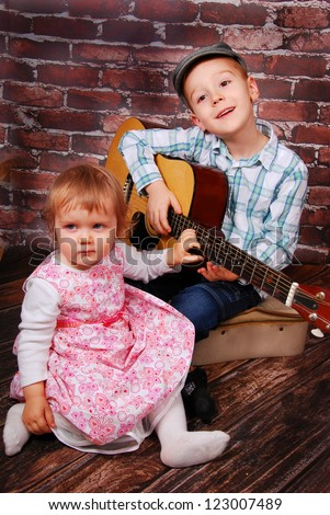 little boy playing the guitar and baby girl sitting in front of him
