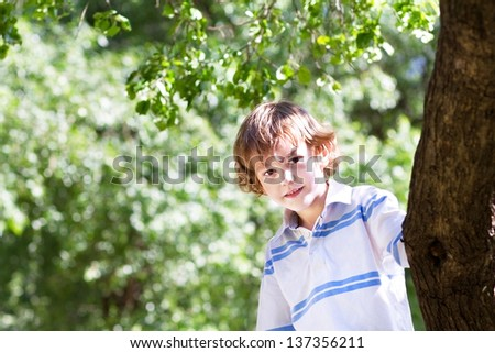 Little boy playing under a big tree on a sunny day