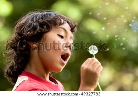 Little boy playing with a flower outdoors