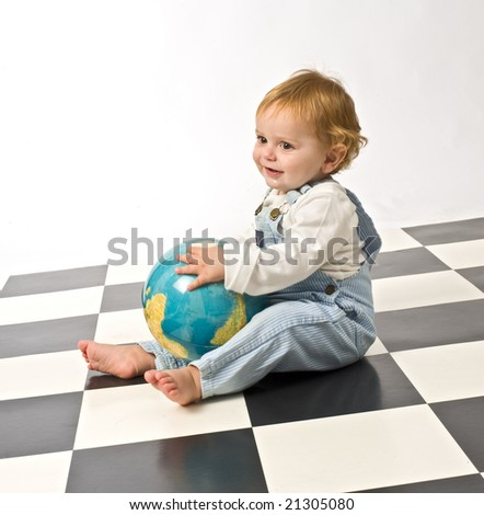 little boy playing with a globe on a checkered floor