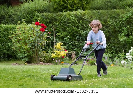 Little boy playing with a lawn mower in the garden