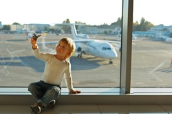 Little boy playing with a toy airplane in airport