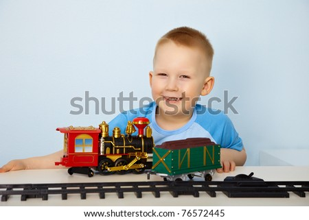 Little boy playing with a toy railway