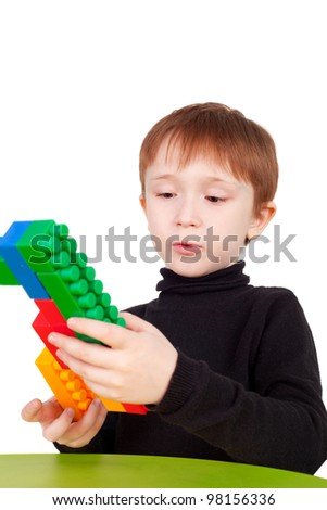 little boy playing with bricks making the pistol