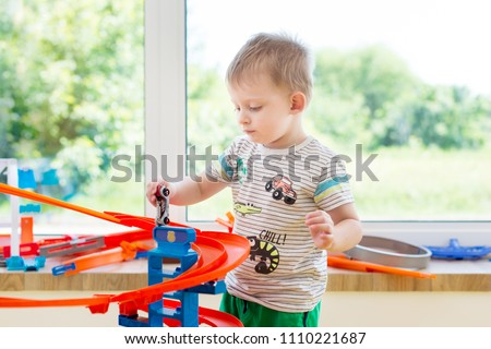 little boy playing with cars in the game center #1110221687