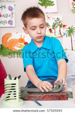 Little boy playing with clay.