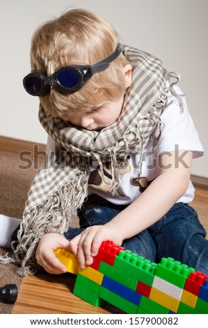 Little boy playing with constructor on floor at home with goggles on his head and scarf around neck