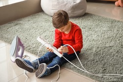 Little boy playing with electric extension cord and iron at home