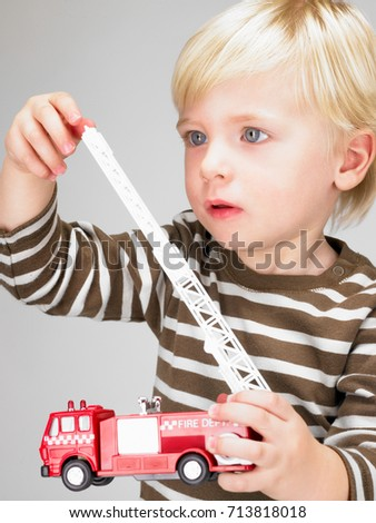 Stock Photo Little boy playing with fire truck