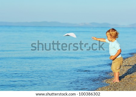 Little boy playing with paper airplane on the beach