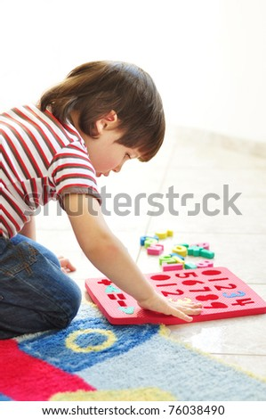 Little boy playing with puzzles on the floor