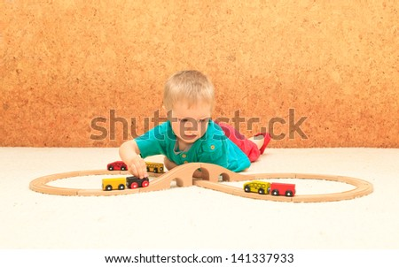 little boy playing with railroad toy
