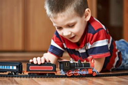 Little boy playing with railway lying on the floor