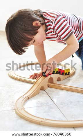 Little boy playing with toy train - stock photo