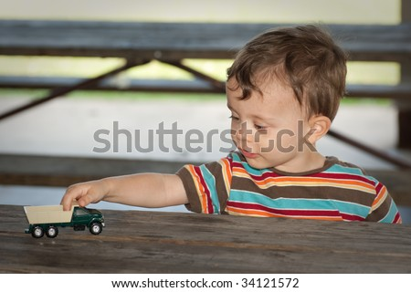 Little boy playing with toy truck