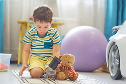 little boy plays alone in a children's room and uses a smart house card to listen to fairy tales.