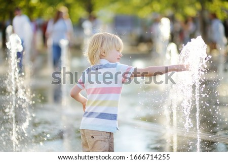 Little boy plays in the square between the water jets in the fountain at sunny summer day. Active summer leisure for kids in the city.