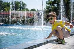 Little boy plays in the square near pool with water jets in the fountain at sunny summer day. Active summer leisure for kids in the city.